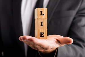 Businessman holding wooden alphabet blocks reading - Lie - balanced in the palm of his hand.